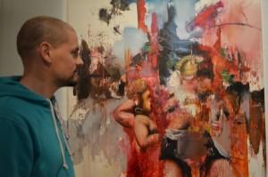 """Flo EYMANN devant son œuvre intitulée """"Femen à l'enfant"""", le soir du vernissage."""